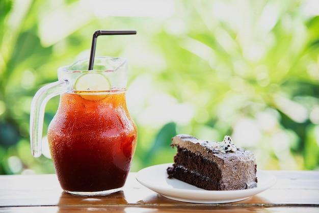 Pastel de chocolate en la mesa con té helado en el jardín verde - relájese con una bebida y una panadería en concepto de naturaleza