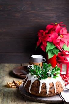 Pastel de chocolate de navidad con glaseado blanco y granos de granada en una madera oscura con linterna roja y flor de pascua