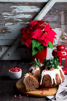 Pastel de chocolate en rodajas de navidad con glaseado blanco y granos de granada de madera oscura con linterna roja y flor de pascua