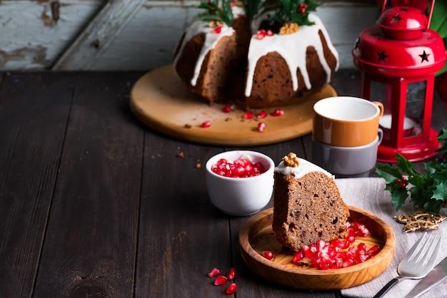 Pastel de chocolate en rodajas de navidad con glaseado blanco y granos de granada de madera oscura, tazas y decoraciones,