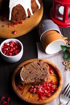 Pastel de chocolate en rodajas de navidad con glaseado blanco y granos de granada, un plano de madera oscuro y plano