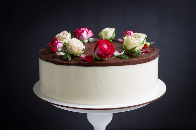 Pastel de chocolate con rosas en soporte vintage. hermoso pastel con flores rosas rojas y blancas, fondo negro