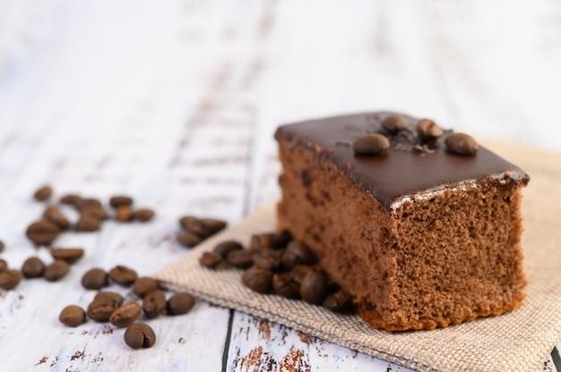 Pastel de chocolate en el saco con granos de café sobre una mesa de madera.