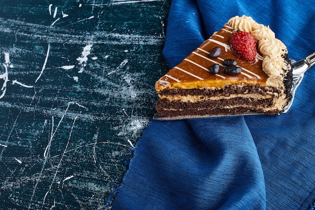 Pastel de chocolate servido con fresas sobre fondo azul.
