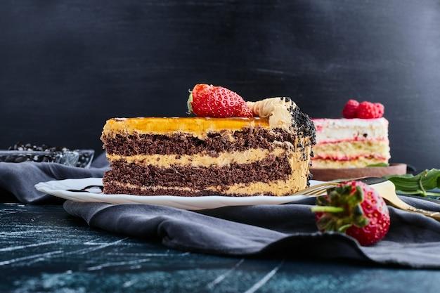Pastel de chocolate servido con frutos rojos sobre fondo azul.