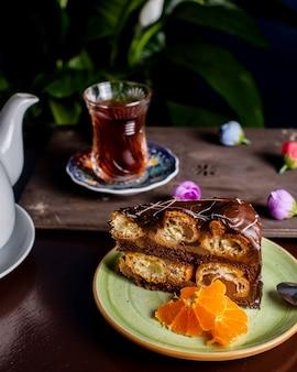 Pastel de chocolate servido con rodajas de naranja y té