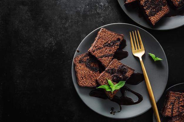 Pastel de chocolate servido con salsa de chocolate.