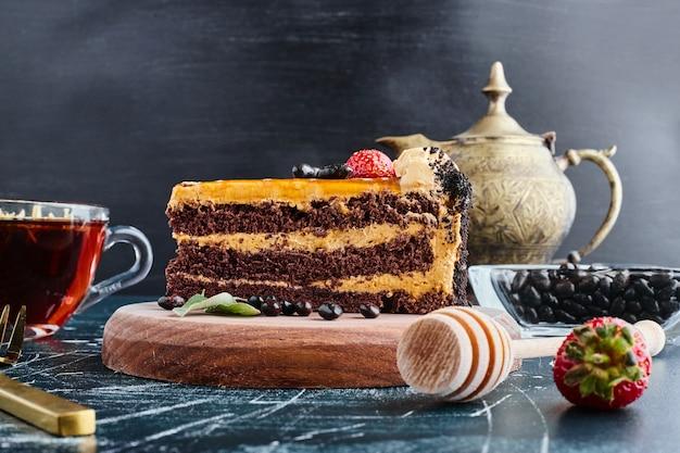 Pastel de chocolate servido con un vaso de té.