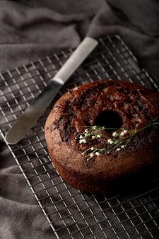 Pastel de chocolate sobre un fondo gris con un cuchillo