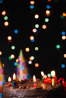 Pastel de chocolate con velas iluminadas y decorado con luces borrosas.