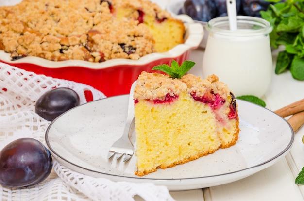 Pastel con ciruelas y shtreisel en un plato sobre una superficie de madera blanca