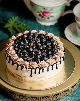 Pastel clásico decorado con jarabe de chocolate y arándanos