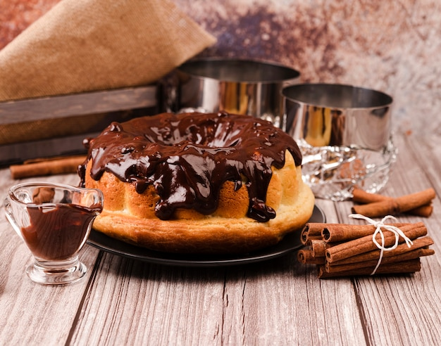 Pastel con cobertura de chocolate y palitos de canela