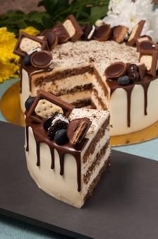 El pastel cortado está decorado con cubitos de chocolate con leche y bayas.