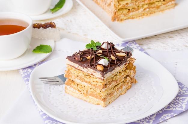 Pastel con crema de caramelo, merengue, maní y glaseado de chocolate