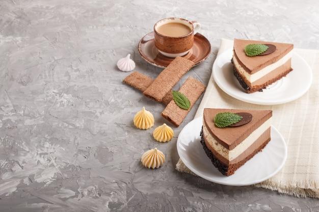 Pastel con crema de chocolate con leche souffle con taza de café sobre un fondo de hormigón gris. vista lateral, copia espacio.