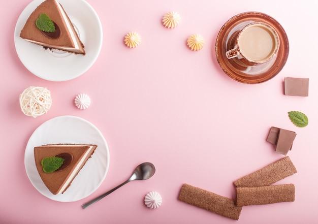 Pastel con crema de chocolate con leche souffle con taza de merengues de café sobre un fondo rosa pastel