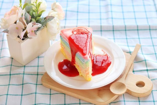 Pastel de crepe de arco iris con mermelada de fresa en una mesa de picnic