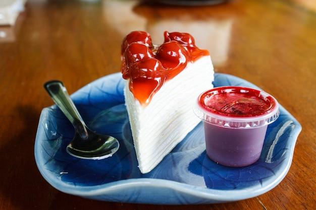 Pastel de crepe cubierto con cerezas y mermelada para cubrir