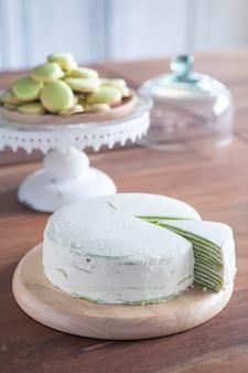Pastel de crepe de té verde y macarrón en mesa de madera