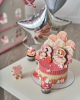 Pastel de cumpleaños para 3 años decorado con mariposas gatito de pan de jengibre con glaseado y el número tres. merengue de color rosa pálido en forma de rosa o flor. el merengue es mucha decoración de pasteles