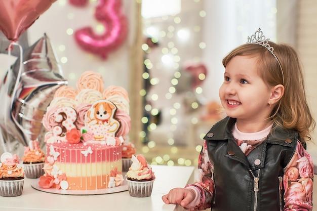 Pastel de cumpleaños para 3 años decorado con mariposas, gatito de pan de jengibre con glaseado y el número tres.