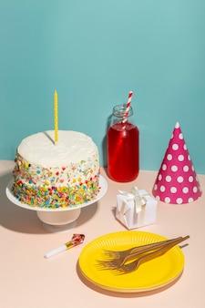 Pastel de cumpleaños de alto ángulo y gorro de fiesta