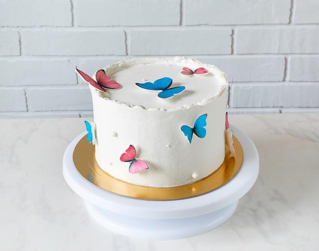 Pastel de cumpleaños blanco decorado con mariposas azules y rojas.
