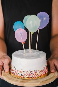 Pastel de cumpleaños blanco y globos de colores sobre gris claro.aniversario de concepto de alimentos.