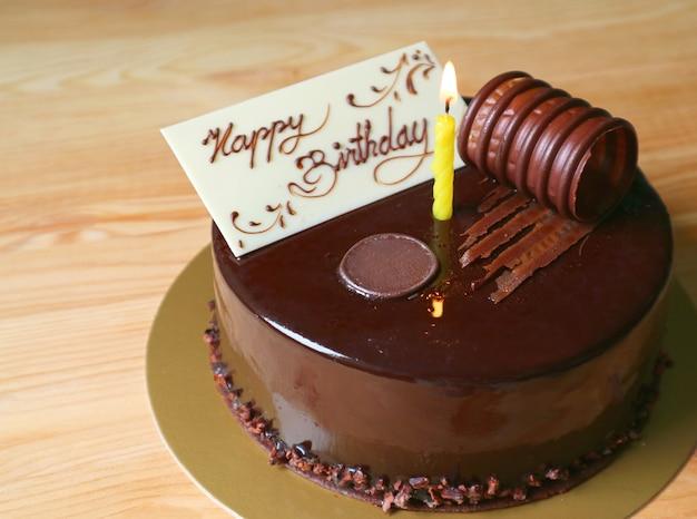 Pastel de cumpleaños de chocolate húmedo cubierto con una tarjeta de felicitación de chocolate blanco comestible y una vela encendida