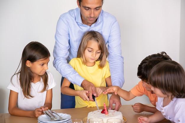 Pastel de cumpleaños de corte de niña linda con la ayuda del padre. niños adorables felices celebrando el cumpleaños juntos y esperando el postre en el comedor. concepto de infancia, celebración y vacaciones.