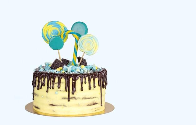 Pastel de cumpleaños con decoración amarilla y azul y cobertura de chocolate.