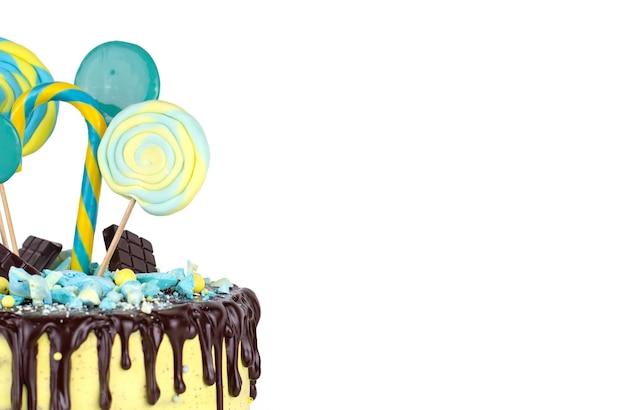 Pastel de cumpleaños con decoración amarilla y azul y glaseado de chocolate en una pared blanca aislada