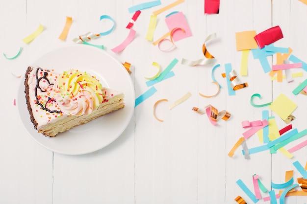 Pastel de cumpleaños y decoración en fondo blanco de madera