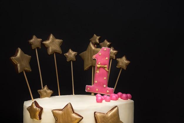 Pastel de cumpleaños decorado con rosa número 1 y estrellas doradas de pan de jengibre.