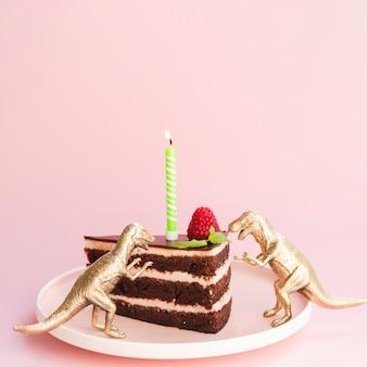 Pastel de cumpleaños y dinosaurios sobre fondo rosa