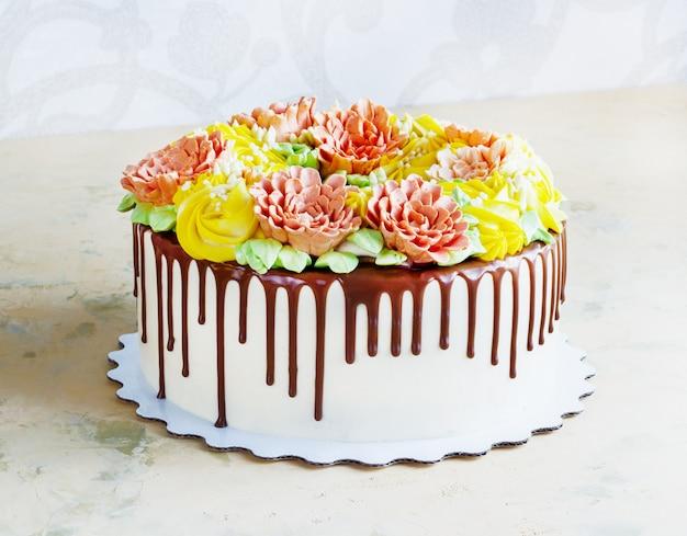 Pastel de cumpleaños con flores rosa en blanco
