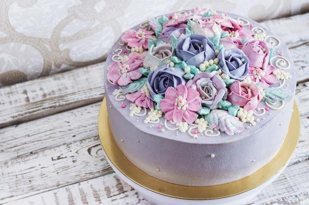Pastel de cumpleaños con flores rosa sobre fondo blanco.
