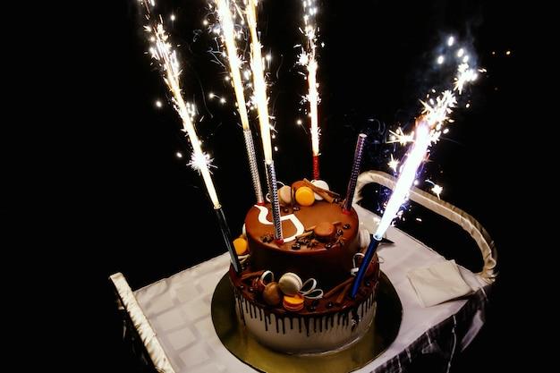 Pastel de cumpleaños con fuegos artificiales en la mesa en superficie negra