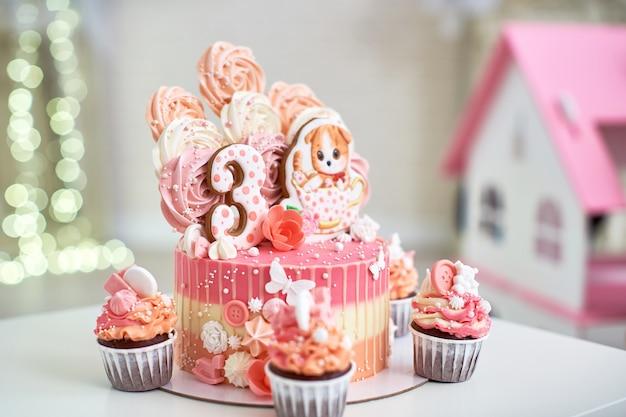 Pastel de cumpleaños con un gatito de pan de jengibre y el número tres.