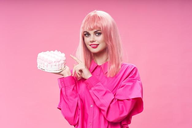 Pastel de cumpleaños en mano de mujer de pelo rosa