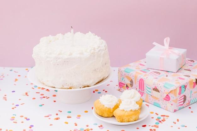 Pastel de cumpleaños; muffins y cajas de regalo con confeti en el escritorio blanco sobre fondo rosa