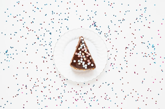 Pastel de cumpleaños en rodajas con confeti