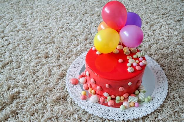 Pastel de cumpleaños rojo casero con globos aerostáticos