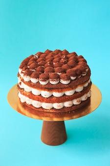 Pastel de cumpleaños en el soporte de la torta de madera. hermoso bizcocho de chocolate con crema batida aderezado con cacao espolvoreado. fondo azul. copie el espacio. fotografía de alimentos para receta.