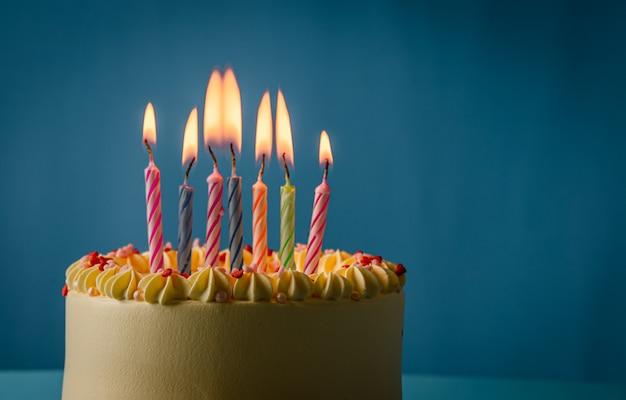 Pastel de cumpleaños con velas de colores sobre fondo de color azul