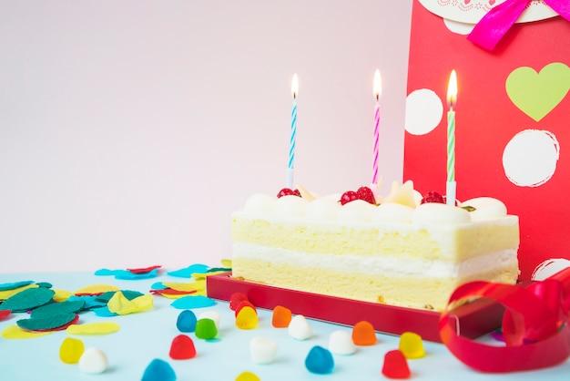 Pastel de cumpleaños con velas encendidas; caramelos y bolso de compras
