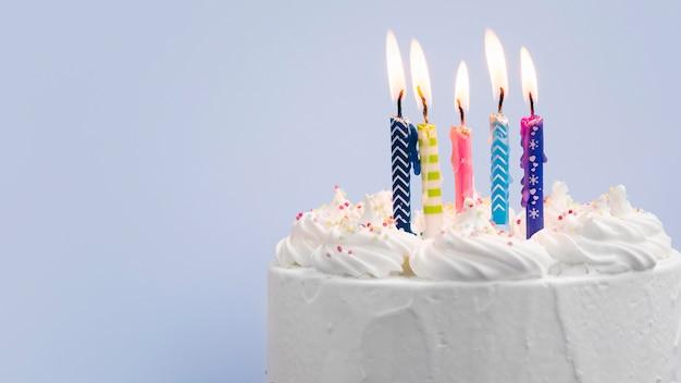 Pastel de cumpleaños con velas sobre fondo azul.