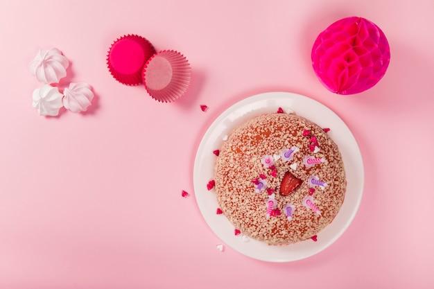 Pastel de cumpleaños con velas; zephyrs; soporte para cupcakes de papel y bolas de papel de nido de abeja pom-pom sobre fondo rosa