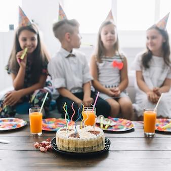 Pastel de cumpleaños y bebidas cerca de los niños